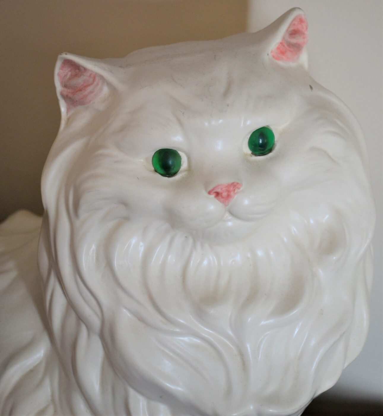 A white porcelain cat with green eyes.